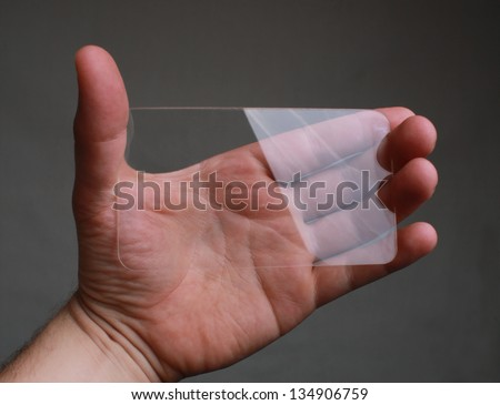Transparent Mobile displayed by hand Horizontallly - stock photo