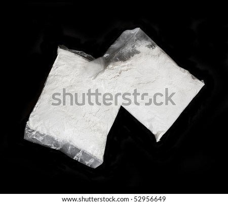 Transparent plastic bags with white powder, isolated on black background - stock photo