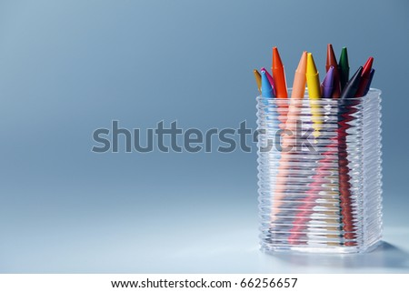 Transparent plastic box filled with crayons.