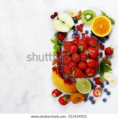 Transparent plastic tray with freshly picked strawberries and fresh fruits - stock photo