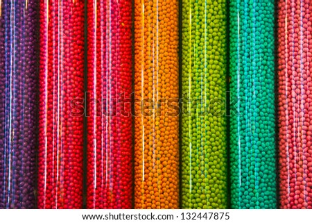 Transparent plastic tubes full of thousands of colorful candies - stock photo