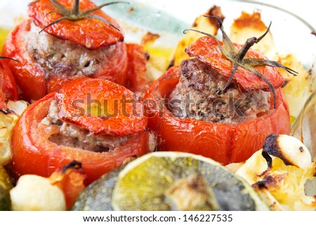 Transparent plate with cooked tomatoes and marrows stuffed with minced meat with sauce. - stock photo
