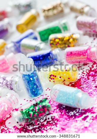 Transparent small bottles with glitter makeup and nail art, selective focus - stock photo