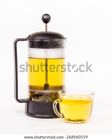 Transparent tea pot and cup of tea with green tea - stock photo