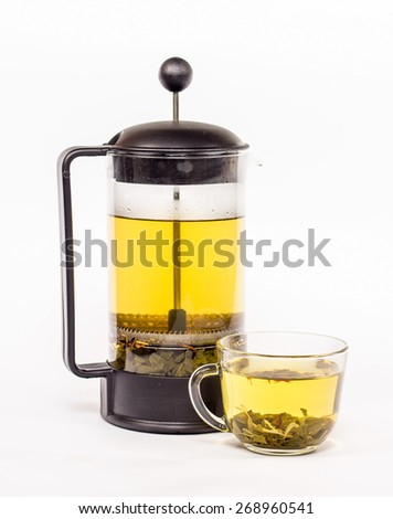 Transparent tea pot and cup of tea with yellow tea. Isolated on white background. - stock photo