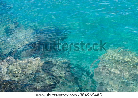 Transparent turquoise water near rocky coast, ripple on surface - stock photo