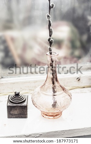 transparent vase with willow branch on the old window sill - stock photo