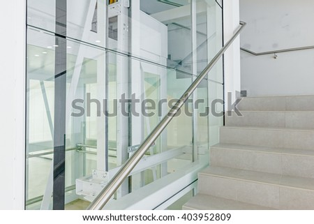 Transparent walls in elevator and staircase in modern building. - stock photo