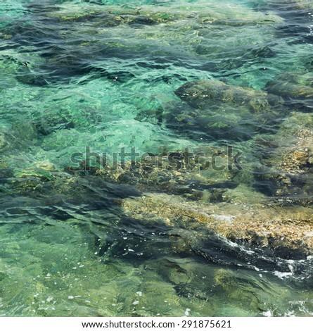 transparent water ripple, marine rocks and sunlight glare. sea floor wallpaper - stock photo