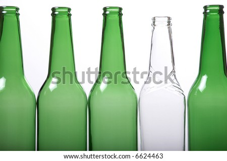 Transparent white beer bottle among green bottles. White background. Concept of difference.