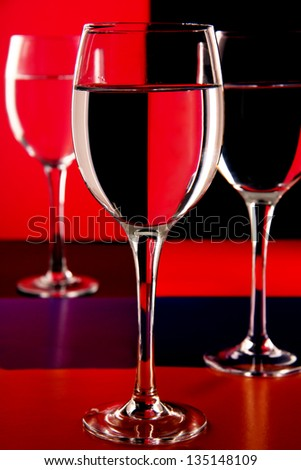 transparent wine glasses on the high leg on a colored background.