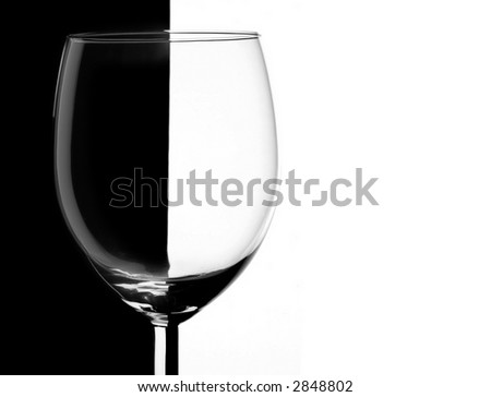 Transparent wineglass over contrast black and white background - stock photo