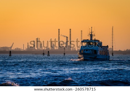Transport boat leaving the petroleum refinery during sunset - stock photo