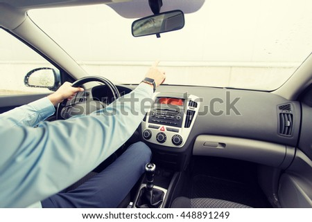 transport, business trip, direction and people concept - close up of young man driving car and pointing finger to something
