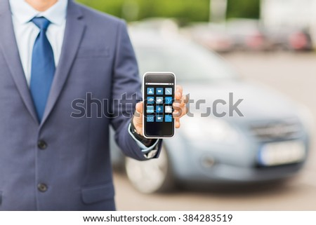 transport, business trip, multimedia, technology and people concept - close up of man showing menu icons smartphone screen on car parking - stock photo