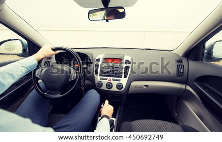 transport, business trip, speed, destination and people concept - close up of young man driving on car parking - stock photo
