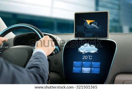 transport, business trip, technology and people concept - close up of businessman driving car with navigator on tablet pc and on board computer showing weather forecast - stock photo