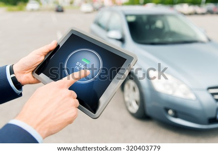 transport, business trip, technology and people concept - close up of male hands pushing start engine button on tablet pc computer screen with car outdoors - stock photo