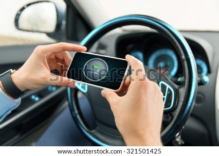 transport, business trip, technology and people concept - close up of male hands with start engine button on smartphone screen in car - stock photo