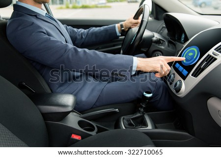 transport, business trip, technology and people concept - close up of young man in suit driving car and adjusting car eco mode system settings on dashboard computer screen - stock photo