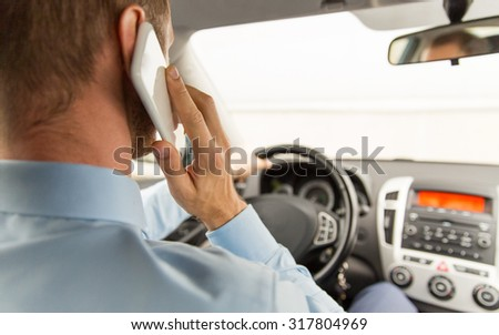 transport, business trip, technology and people concept - close up of young man with smartphone driving car - stock photo