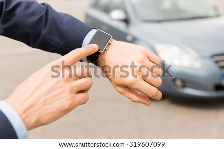 transport, business trip, technology, time and people concept - close up of male hands with wristwatch on car parking - stock photo