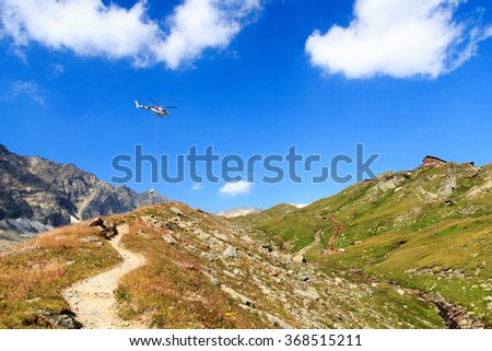 Transport helicopter flying with supplies and mountain panorama with alpine hut in Hohe Tauern Alps, Austria - stock photo