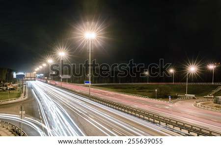 transport metropolis, traffic and blurry lights of cars on multi-lane highways and dense road traffic at night in Moscow - stock photo