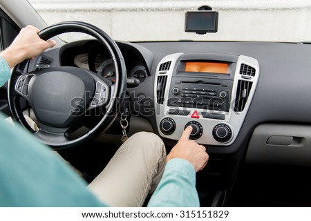transport, road trip, car driving, technology and people concept - close up of male hand using climate control in car - stock photo