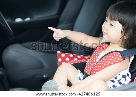 Transport, safety, childhood road trip and people concept - happy little girl sitting in baby car seat, Child in auto baby seat in car, Adorable little girl in the car. - stock photo