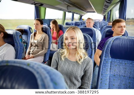 transport, tourism, road trip and people concept - young woman with group of passengers or tourists in travel bus