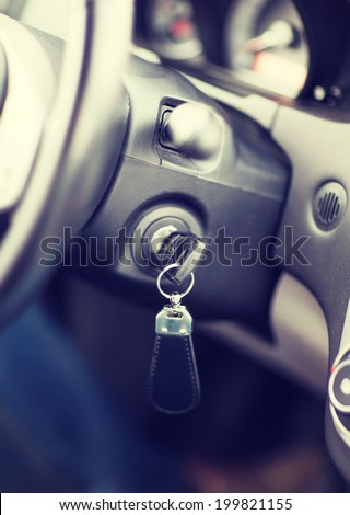 transportation and ownership concept - car key in ignition start lock - stock photo