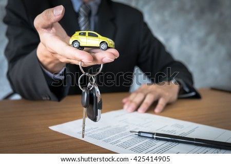 transportation and ownership concept - customer and salesman with car key - stock photo
