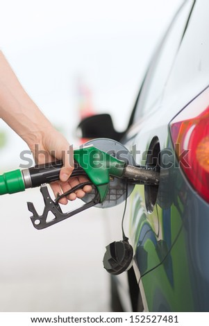 transportation and ownership concept - man pumping gasoline fuel in car at gas station - stock photo