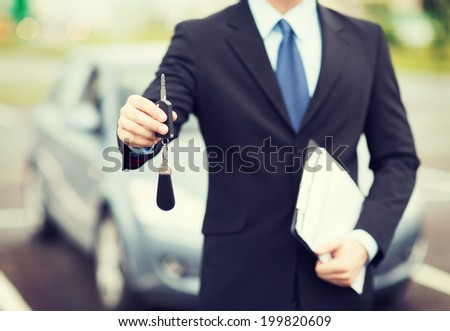 transportation and ownership concept - man with car key outside - stock photo