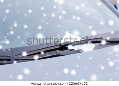 transportation and vehicle concept - close up of parking ticket on car windscreen - stock photo
