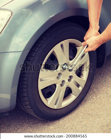 transportation and vehicle concept - man changing tire - stock photo