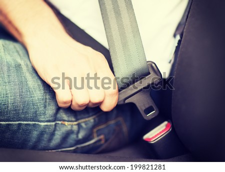 transportation and vehicle concept - man fastening seat belt in car - stock photo