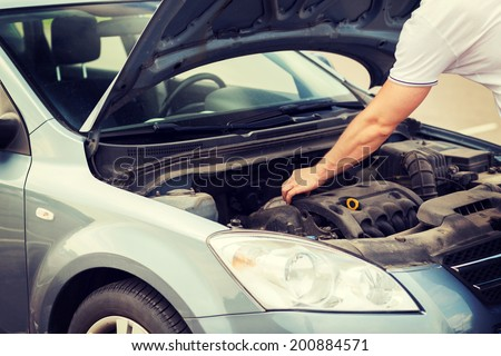 transportation and vehicle concept - man opening car bonnet and looking under hood - stock photo