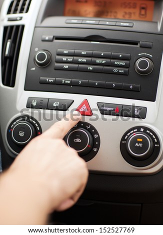 transportation and vehicle concept - man pressing red triangle car hazard warning button