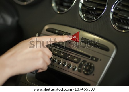 transportation and vehicle concept - man pressing red triangle car hazard warning button - stock photo