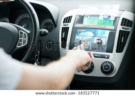 transportation and vehicle concept - man using car control panel to read news - stock photo