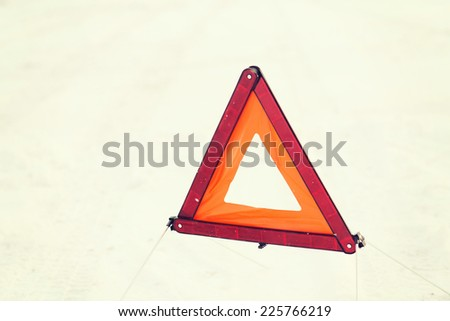 transportation and winter concept - closeup of warning triangle on snow