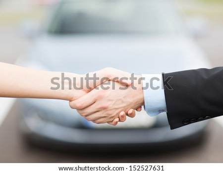 transportation, business, shopping and ownership concept - customer and salesman shaking hands outside - stock photo