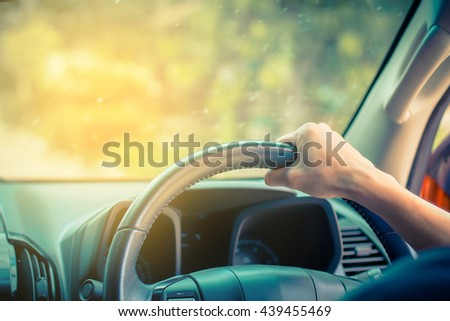Transportation,Businessman driving back home after exhausting day at work,Hands of a driver on steering wheel of a car ,Car driving with both hands on the wheel,selective focus,vintage color   - stock photo