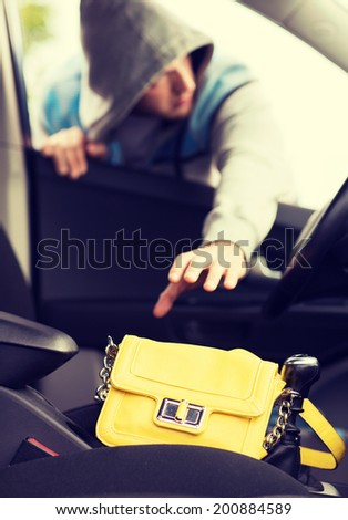transportation, crime and ownership concept - thief stealing bag from the car - stock photo