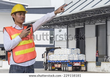 transportation engineer control truck loading product at warehouse building - stock photo