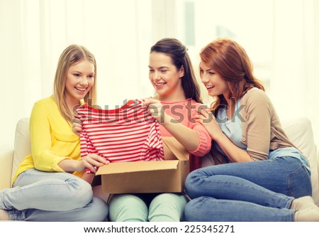 transportation, post and friendship concept - three smiling teenage girls opening cardboard box at home - stock photo