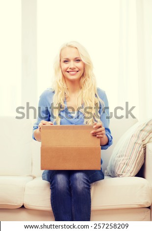 transportation, post and people concept - smiling young woman opening cardboard box at home - stock photo