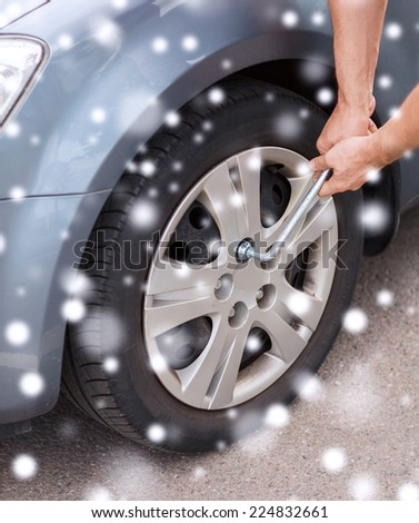 transportation, repair, people and vehicle concept - man changing tire - stock photo